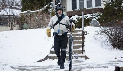 In this Thursday, Jan. 26, 2017 photo, Dan Hansen leaves his northeast Minneapolis home before mounting his unicycle for his commute to downtown Minneapolis. For the last three and a half years, Hansen has ridden his unicycle almost every day from his home in northeast Minneapolis to the Mill City Museum, where he's responsible for the upkeep of the historic building. (Evan Frost/Minnesota Public Radio via AP)