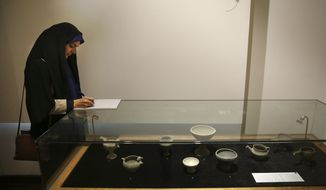 In this photo taken on Monday, Feb. 6, 2017, an Iranian journalist takes note as she covers a show displaying some 550 ancient Persian artworks returned by Western countries, including the United States, at Iran National Museum in Tehran, Iran. (AP Photo/Vahid Salemi)
