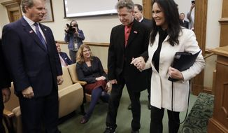 Country singer Randy Travis, center, walks into a hearing room with his wife, Mary, before a meeting of the Senate Health and Welfare Committee on Wednesday, Feb. 8, 2017, in Nashville, Tenn. Randy Travis, who suffered a stroke in 2013, attended the hearing for Stroke Awareness Day at the legislature. Dozens of country stars, from Garth Brooks to Kenny Rogers, are scheduled to perform at a tribute show Wednesday night in Nashville to honor Travis. At left is Sen. Bill Ketron, R-Murfreesboro. (AP Photo/Mark Humphrey)