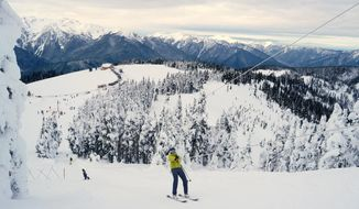 This photo taken Jan. 7, 2017, shows a skier nears the top of the rope tow at Hurricane Ridge in Olympic National Park, Wash. The visitor center is in the background. (Caitlin Moran / The Seattle Times via AP)