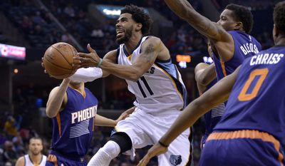 Memphis Grizzlies guard Mike Conley (11) shoots between Phoenix Suns guards Eric Bledsoe, second from right, and Devin Booker (1) in the second half of an NBA basketball game Wednesday, Feb. 8, 2017, in Memphis, Tenn. (AP Photo/Brandon Dill)