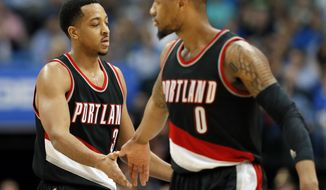 Portland Trail Blazers' C.J. McCollum (3) and Damian Lillard (0) celebrate a basket by McCollum against the Dallas Mavericks during the second half of an NBA basketball game in Dallas, Tuesday, Feb. 7, 2017. McCollum had 32 points and Lillard had 29 in the team's 114-113 win. (AP Photo/Tony Gutierrez)