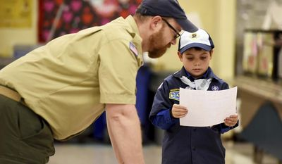 """In this Feb. 7, 2017 photo, Joe Maldonado, the first openly transgender member of the Boy Scouts, looks at his Boy Scout application with Scout leader Kyle Hackler in Maplewood, N.J. Boy Scouts of America recently changed its policy to allow transgender children to join the organization. """"I am accepted,"""" Maldonado said as he put on the uniform. (Amy Newman/The Record via AP)"""