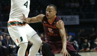 Virginia Tech's Justin Robinson (5) drives to the basket as Miami's Dejan Vasiljevic (4) defends during the first half of an NCAA basketball game, Wednesday, Feb. 8, 2017, in Coral Gables, Fla. (AP Photo/Lynne Sladky)