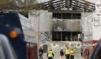 FILE - This Dec. 7, 2016 file photo members of the Alameda County Sheriff's Office stand outside the warehouse called the Ghost Ship the site of a fire, in Oakland, Calif. Oakland police visited the cluttered warehouse converted into an illegal residence dozens of times in the several years before it burned down, killing 36 people. Oakland officials on Wednesday, Feb. 8, 2017 released hundreds of pages of city documents requested by The Associated Press and other media outlets. The reports detail complaints from neighbors, residents and visitors of the so-called Ghost Ship warehouse about safety problems, loud parties and other issues with a dilapidated building converted illegally into a living area. (AP Photo/Eric Risberg,File)