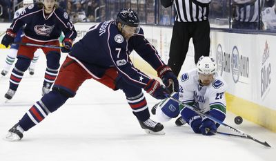 Vancouver Canucks' Daniel Sedin, right, of Sweden, and Columbus Blue Jackets' Jack Johnson chase the puck during the first period of an NHL hockey game Thursday, Feb. 9, 2017, in Columbus, Ohio. (AP Photo/Jay LaPrete)