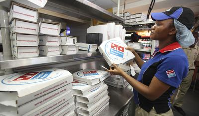 FILE - In this Sunday, Feb. 10, 2013, file photo, a worker prepares boxes at a Domino's pizza restaurant in Lagos, Nigeria. Domino's announced on Feb. 8, 2017, that it launched a wedding registry site just in time for Valentine's Day. (AP Photo/Sunday Alamba, File)