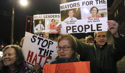 """FILE - In this Monday, Feb. 6, 2017, file photo, people hold signs during a rally to advocating to make Bridgeport a sanctuary city outside City Hall in Bridgeport, Conn. Bridgeport Mayor Joe Ganim has questioned how much of the demand is coming not from inside his city but rather the neighboring, more affluent suburban towns. He held his own demonstration across the city line at the Fairfield rail station, and posted a photo of himself on social media with a sign declaring """"Make Fairfield a Sanctuary City!"""" (Brian A. Pounds/Hearst Connecticut Media via AP)"""