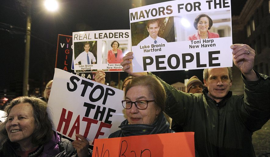 In this Monday, Feb. 6, 2017, file photo, people hold signs during a rally to advocating to make Bridgeport a sanctuary city outside City Hall in Bridgeport, Conn. (Brian A. Pounds/Hearst Connecticut Media via AP) ** FILE **