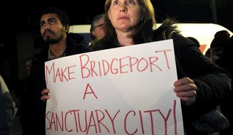 """FILE - In this Monday, Feb. 6, 2017, file photo, Ann McCarthy, of Fairfield, attends a rally to make Bridgeport a sanctuary city outside City Hall in Bridgeport, Conn. Bridgeport Mayor Joe Ganim seized on the presence of the Fairfield resident at the protest and held his own demonstration across the city line at the Fairfield rail station. On social media, he posted a photo of himself with a sign declaring """"Make Fairfield a Sanctuary City!"""" (Brian A. Pounds/Hearst Connecticut Media via AP)"""