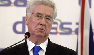 British Defense Secretary Sir Michael Fallon listens to a journalist's question during a joint statement with Italian Minister of Defense Roberta Pinotti, following their meeting, in Rome, Thursday, Feb. 9, 2017. (AP Photo/Alessandra Tarantino)