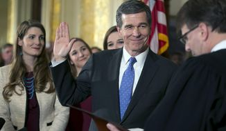 FILE - In this Friday, Jan. 6, 2017, file photo, Roy Cooper is ceremonially sworn in as Governor of North Carolina by Chief Justice Mark Martin during a ceremony at the Executive Mansion in Raleigh, N.C. Cooper's daughters from left, Hilary, Natalie and Claire look on. A North Carolina court has temporarily blocked a state law passed by the GOP-controlled legislature that strips the Democratic governor of his some of his powers. A three-judge panel released the order Wednesday, Feb. 8, 2017, just before state senators scheduled a hearing with the secretary of Cooper's veterans' affairs department to come before a committee to answer questions. (Robert Willett/The News & Observer via AP, File)