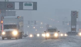 Vehicles drive drive through snow as they approach the Holland Tunnel, Thursday, Feb. 9, 2017, in Jersey City, N.J. A powerful, fast-moving storm swept through the northeastern U.S. early Thursday, making for a slippery morning commute and leaving some residents bracing for blizzard conditions. (AP Photo/Julio Cortez)