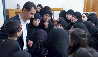 "In this photo released on Thursday, Feb. 9, 2017, by the Syrian official news agency SANA, President Bashar Assad meets with former hostages released in an prisoner exchange with rebels, in Damascus, Syria. The ""First Coastal Division"" rebel faction released 55 women and children detainees on Tuesday in exchange for the government releasing 54 women prisoners of its own. (SANA via AP)"