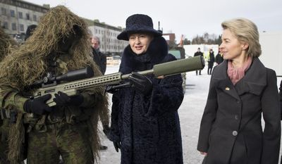 German Defense Minister Ursula von der Leyen, right, and Lithuania's Presidend Dalia Grybauskaite speaks with a soldier during the NATO enhanced forward presence battalion welcome ceremony at the Rukla military base some 130 km (80 miles) west of the capital Vilnius, Lithuania, Tuesday, Feb. 7, 2017. The NATO enhanced forward presence battalion in Lithuania will be led by framework nation Germany. (AP Photo/Mindaugas Kulbis)