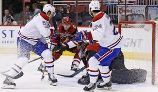 Montreal Canadiens left wing Max Pacioretty (67) scores a goal against Arizona Coyotes goalie Mike Smith, right, as Canadiens left wing Phillip Danault (24) and Coyotes' defenseman Luke Schenn (2) watch during the first period of an NHL hockey game Thursday, Feb. 9, 2017, in Glendale, Ariz. (AP Photo/Ross D. Franklin)