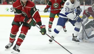 Minnesota Wild's Marco Scandella (6) keeps the puck away from Tampa Bay Lightning's J.T. Brown (23) during the second period of an NHL hockey game Friday, Feb. 10, 2017, in St. Paul, Minn. (AP Photo/Stacy Bengs)