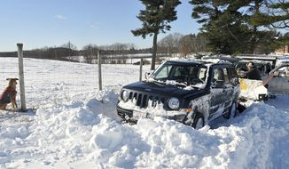 Jim McGrath works to get his vehicle free from a snow bank at a dog park in Wrentham, Mass., Friday, Feb.10, 2017, one day after a snowstorm.  (Mark Stockwell/The Sun Chronicle via AP)