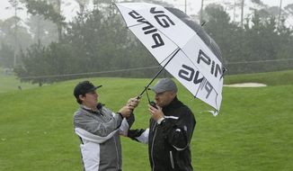 Joel Dahmen, left, holds an umbrella for a rules official while waiting for a ruling below the ninth green of the Spyglass Hill Golf Course during the first round of the AT&T Pebble Beach National Pro-Am golf tournament Thursday, Feb. 9, 2017, in Pebble Beach, Calif. (AP Photo/Eric Risberg)