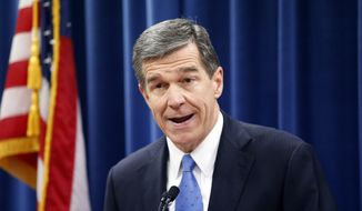 FILE - In this Dec. 15, 2016 file photo, North Carolina's Governor-elect Roy Cooper holds a news conference to criticize efforts by Republicans to cut the power of the governor's office during the special session of the General Assembly that is going on a few blocks away in Raleigh, N.C.   Republican efforts to reduce Cooper's authority in choosing his Cabinet are back in court. A three-judge panel scheduled arguments Friday, Feb. 10, 2017,  on whether to extend their recent temporary block of a law requiring Senate confirmation of Cooper's Cabinet secretaries.(Chris Seward /The News & Observer via AP, File)