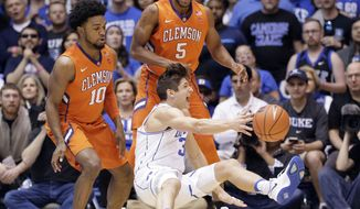 Duke's Grayson Allen (3) falls to the floor as Clemson's Gabe DeVoe (10) and Jaron Blossomgame (5) defend during the first half of an NCAA college basketball game in Durham, N.C., Saturday, Feb. 11, 2017. (AP Photo/Gerry Broome)