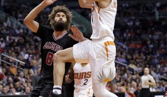 Phoenix Suns guard Devin Booker (1) drives as Chicago Bulls center Robin Lopez (8) defends during the second half of an NBA basketball game, Friday, Feb. 10, 2017, in Phoenix. (AP Photo/Matt York)