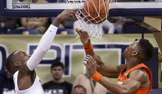CORRECTS ID TO PITTSBURGH'S MICHAEL YOUNG, NOT CRISSHAWN CLARK - Pittsburgh's Michael Young, left, dunks in front of Syracuse's Andrew White III during the first half of an NCAA college basketball game, Saturday, Feb. 11, 2017, in Pittsburgh. (AP Photo/Keith Srakocic)