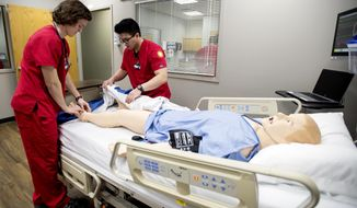 ADVANCE FOR USE SATURDAY, FEB. 11 - In this Feb. 2, 2017 photo, nursing students Zach Krall, left,  and Anthony Waworoendeng examine a simulator manikin in the Nursing Simulation Center during an open house at Union College in Lincoln, Neb. The Nursing Simulator Center,  just opened a $350,000 expansion in January, gives 100 students the chance to practice hard skills like starting an IV or fitting a central line. (Kristin Streff/The Journal-Star via AP)
