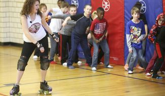 In this Friday, Feb. 3, 2017 photo, fourth-grade teacher Daniele Halfhill teaches her students roller derby skills at Fulton Elementary School in Dubuque, Iowa. (Jessica Reilly/Telegraph Herald via AP)