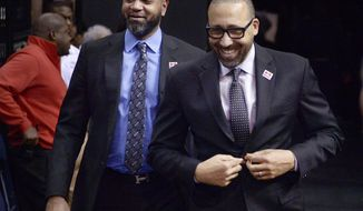 ADVANCE FOR USE SATURDAY, FEB. 11 - In this Feb. 8, 2017 photo, Memphis Grizzlies head coach David Fizdale, right, and associate head coach J. B. Bickerstaff walk to the court for an NBA basketball game against the Phoenix Suns in Memphis, Tenn. Fizdale and longtime friend Bickerstaff have teamed up in Memphis, and their chemistry is a big reason why the Grizzlies have been one of the surprise teams in the NBA this season. (AP Photo/Brandon Dill)