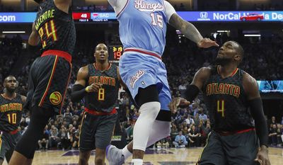 Sacramento Kings forward DeMarcus Cousins, center, goes to the basket between Atlanta Hawks' Kent Bazemore, left, and Paul Millsap during the first half of an NBA basketball game Friday, Feb. 10, 2017, in Sacramento, Calif. (AP Photo/Rich Pedroncelli)