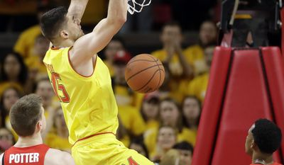 Maryland forward Michal Cekovsky, center, of Slovakia, dunks on Ohio State center Micah Potter, bottom left, and guard C.J. Jackson in the first half of an NCAA college basketball game, Saturday, Feb. 11, 2017, in College Park, Md. (AP Photo/Patrick Semansky)