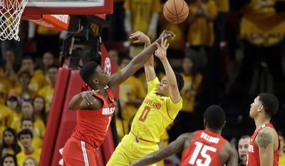 Ohio State forward Jae'Sean Tate, left, blocks a shot-attempt by Maryland guard Anthony Cowan (0) in front of teammates Kam Williams (15) and Marc Loving in the first half of an NCAA college basketball game, Saturday, Feb. 11, 2017, in College Park, Md. (AP Photo/Patrick Semansky)