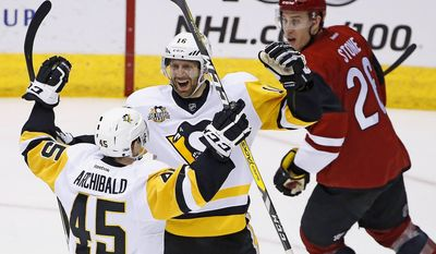 Pittsburgh Penguins right wing Josh Archibald (45) celebrates his goal with center Eric Fehr (16) as Arizona Coyotes defenseman Michael Stone, right, looks on during the second period of an NHL hockey game, Saturday, Feb. 11, 2017, in Glendale, Ariz. (AP Photo/Ross D. Franklin)