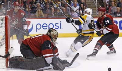Arizona Coyotes goalie Mike Smith (41) makes a save on a shot as Coyotes defenseman Michael Stone (26) pushes Pittsburgh Penguins left wing Scott Wilson, second from right, as Coyotes left wing Brendan Perlini (29) looks on during the first period of an NHL hockey game Saturday, Feb. 11, 2017, in Glendale, Ariz. (AP Photo/Ross D. Franklin)
