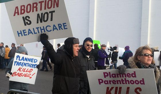 Abortion opponents rally outside Planned Parenthood  in St. Paul, Minn., on Saturday, Feb. 11, 2017.  Rallies aimed at urging Congress and President Donald Trump to end federal funding for Planned Parenthood are scheduled across the country.  (AP Photo/Jeff Baenen)