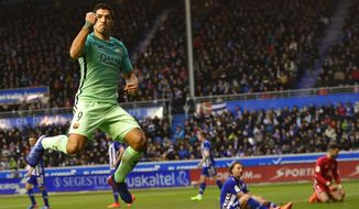 FC Barcelona's Luis Suarez, left, celebrates after scoring his goal in front Alaves's goalkeeper Fernando Pacheco, background right, during the Spanish La Liga soccer match between Barcelona and Deportivo Alaves, at Mendizorroza stadium, in Vitoria, northern Spain, Saturday, Feb.11, 2017. (AP Photo/Alvaro Barrientos)