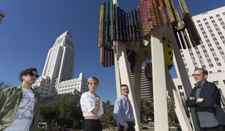 """In this Wednesday, Feb. 1, 2017, photo members of the Triforium project, from left, Jona Bechtolt, Claire Evans, Tom Carroll, and Tanner Blackman,  pose for a photo with Joseph L. Young's Triforium a """"polyphonoptic"""" public sculpture at the Fletcher Bowron Square downtown Los Angeles.  For 40 years Joseph Young festooned public buildings, open spaces and private places across his adopted city of Los Angeles with dozens of brilliant, larger-than-life artworks.  Mocked for 42 years as pointless and silly looking, the six-story, space-age-like structure may finally get a second chance, thanks to a $100,000 innovation grant.. (AP Photo/Damian Dovarganes)"""
