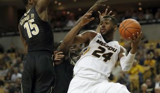 Missouri's Kevin Puryear (24) looks to pass around Vanderbilt's Clevon Brown (15) during the first half of an NCAA college basketball game Saturday, Feb. 11, 2017, in Columbia, Mo. (AP Photo/Jeff Roberson)