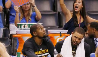 Golden State Warriors forward Kevin Durant looks at the scoreboard as Thunder fans wave cardboard cupcakes above in the fourth quarter of an NBA basketball game against the Oklahoma City Thunder in Oklahoma City, Saturday, Feb. 11, 2017. Warriors center JaVale McGee, right, looks on. (AP Photo/Sue Ogrocki)