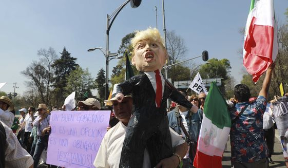 A woman holds a pinata depicting U.S. President Donald Trump during a march demanding respect for Mexico and its migrants, in the face of perceived hostility from the Trump administration, in Mexico City, Sunday, Feb 12, 2017. About 20,000 people, many dressed in white, some carried Mexican flags, as a sign of unity. (AP Photo/Christian Palma)