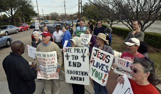 Dallas Police Sgt. Hall, left, speaks with Rives Grogan, 51, of Mansfield, Texas, who wears a red Trump cap, and other anti-abortion protesters, informing them which sidewalks they can use to conduct their protest, outside of the Planned Parenthood South Dallas Surgical Health Services Center, Saturday morning, Feb. 11, 2017, in Dallas. (Ben Torres/The Dallas Morning News via AP) ** FILE **