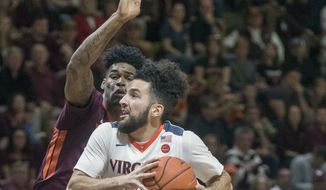 Virginia guard London Perrantes (32) drives on Virginia Tech guard Ahmed Hill (13) during the first half an NCAA college basketball game, Sunday, Feb. 12, 2017, at Cassell Coliseum in Blacksburg, Va. (AP Photo/Don Petersen)