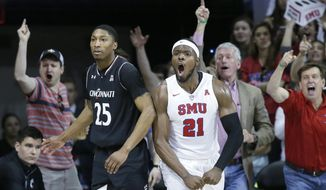 With fans cheering in the background, SMU guard Ben Emelogu II (21) reacts to a call next to Cincinnati guard Kevin Johnson (25) during the second half of an NCAA college basketball game in Dallas, Sunday, Feb. 12, 2017. SMU won 60-51. (AP Photo/LM Otero)