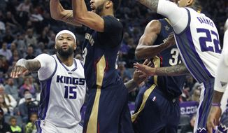 New Orleans Pelicans forward Anthony Davis (23) drives to the basket against Sacramento Kings defenders DeMarcus Cousins (15) and Matt Barnes (22) during the first half of an NBA basketball game in Sacramento, Calif., Sunday, Feb. 12, 2017. (AP Photo/Steve Yeater)