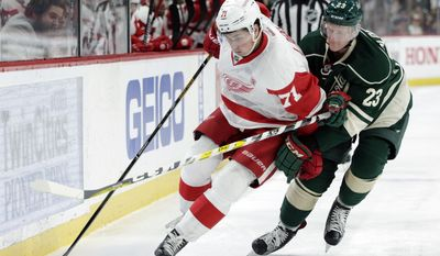 Detroit Red Wings center Dylan Larkin (71) battles Minnesota Wild defenseman Gustav Olofsson (23), of Sweden, for the puck during the second period of an NHL hockey game, Sunday, Feb. 12, 2017, in St. Paul, Minn. (AP Photo/Paul Battaglia)