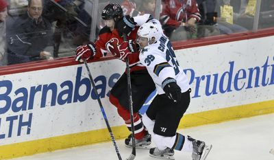 San Jose Sharks center Logan Couture (39) hits New Jersey Devils center Sergey Kalinin (51), of Russia, during the second period of an NHL hockey game, Sunday, Feb. 12, 2017, in Newark, N.J. (AP Photo/Mel Evans)