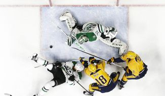 Dallas Stars goalie Kari Lehtonen (32), of Finland, blocks a shot as teammate Jordie Benn (24) reaches for the rebound along with Nashville Predators right wing James Neal (18) and defenseman Yannick Weber (7), of Switzerland, during the first period of an NHL hockey game Sunday, Feb. 12, 2017, in Nashville, Tenn. (AP Photo/Mark Humphrey)