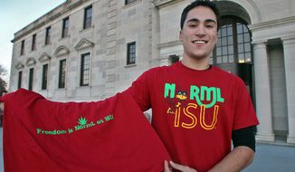 In this photo taken Nov. 15, 2012, Josh Montgomery, the former president of the Iowa State University chapter of the National Organization for the Reform of Marijuana Legislation, displays a T-shirt that shows the organization's logo on the front with an ISU mascot Cy the Cardinal and the NORML logo on the back with a marijuana leaf in Ames, Iowa. Iowa State University lost an appeal Monday, Feb. 13, 2017, in a federal free speech lawsuit centered on the T-shirt design. (Bill Neibergall/The Des Moines Register via AP)