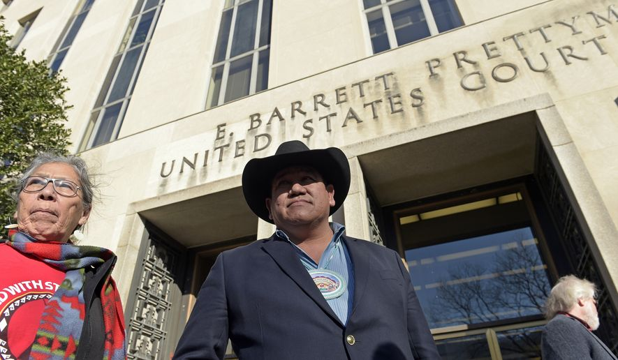 Cheyenne River Sioux Chairman Harold Frazier, center, and Madonna Thunder Hawk, left, of the Oohenumpa band of the Cheyenne River Sioux Tribe, wait to speak to reporters outside federal court in Washington, Monday, Feb. 13, 2017. A judge has rejected a request by two American Indian tribes to halt construction of the remaining section of the Dakota Access oil pipeline until their lawsuit over the project is resolved. (AP Photo/Susan Walsh)